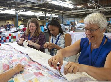 women gathered around a quilt