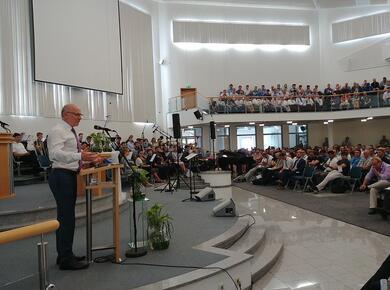 a preacher addresses a full room