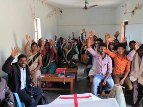 people in a church wave at the camera